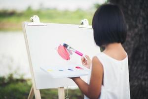 Little girl artist painting a picture in the park photo