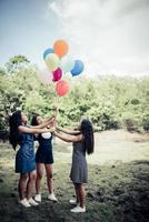 Happy group girlfriends holding multi-colored balloons at a park