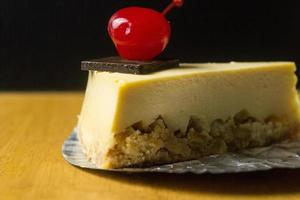 Slice of cheesecake with chocolate and cherry on wood table photo