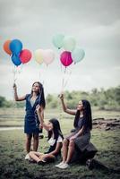 Grupo de novias felices sosteniendo globos multicolores en un parque