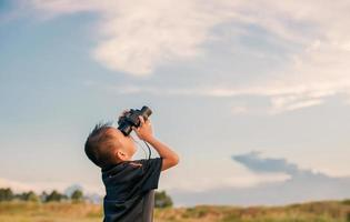 Happy kid playing with binoculars in the meadow