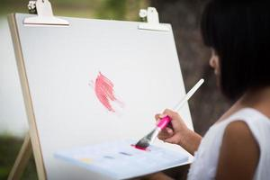Little girl artist painting a picture in the park