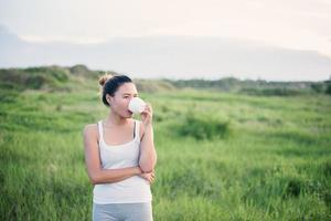Beautiful Asian woman drinking coffee in a meadow