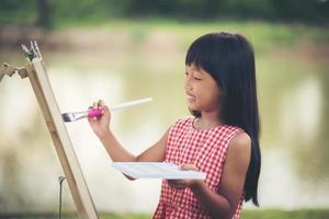 niña artista pintando un cuadro en el parque
