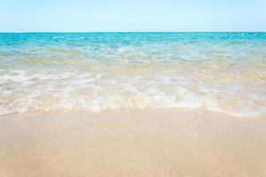 Olas del océano en la playa de arena con cielo azul claro