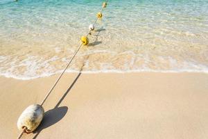 Boyas de cuerda con olas del mar en la playa de arena