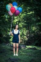 Young girl holding colorful balloons in nature