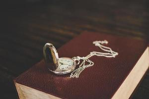 Close up of a vintage pocket watch on old books