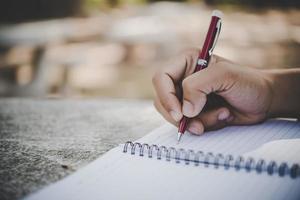 Man handwriting in his notebook