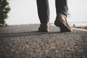 Close-up de joven turista hombre caminando por una carretera rural foto
