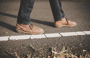 Close-up de joven turista hombre caminando por una carretera rural