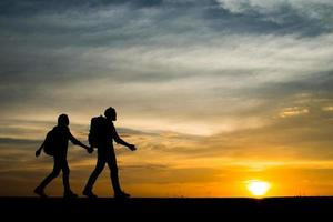 Silhouettes of two hikers with backpacks enjoying the sunset photo