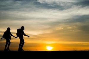 Silhouettes of two hikers with backpacks enjoying the sunset