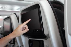 Close-up of hand touching screen in airplane