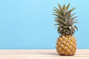 Pineapple on a table with blue background