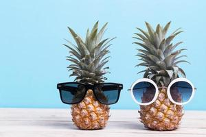Two pineapples wearing sunglasses