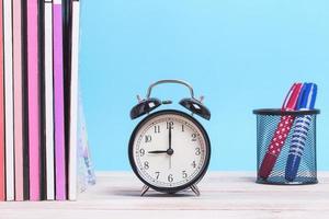 Revistas reloj y marcadores de mesa de madera foto