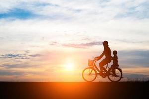 Mother with her child riding bikes at sunset