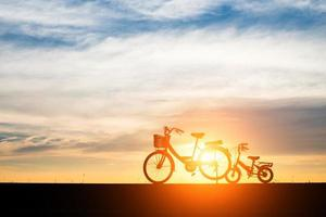Two vintage silhouette bicycles at sunset