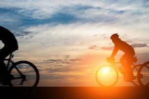 Young man rides a bicycle on sunset background