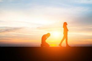 Silhouette of an upset couple in a quarrel at sunset photo