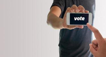 hombre sujetando el teléfono con voto en la pantalla