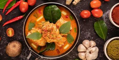 Chicken curry in a pan with lemongrass, kaffir lime leaves, tomatoes, lemon, and garlic photo