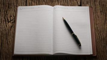 Image of an open blank notebook on wooden table photo