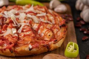 Pizza on a wooden board with bell peppers, garlic, chili and shiitake mushrooms