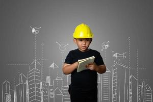 Young boy wearing a yellow engineer hat and house plan ideas on a blackboard