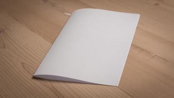 Papel doblado en blanco blanco sobre mesa de madera