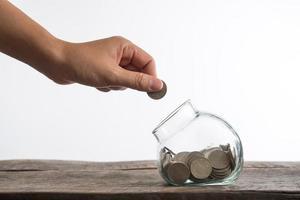manos poniendo dinero en una botella por dinero en efectivo en el futuro
