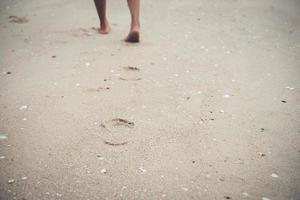 Young woman standing on the beach with bare feet photo