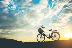 Silhouette of a bicycle parked on a mountain photo