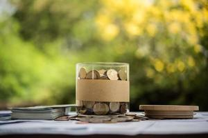 Money in a glass jar in nature, investment concept