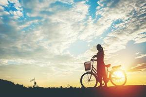 Silhouette of a woman with a bicycle and beautiful sky photo