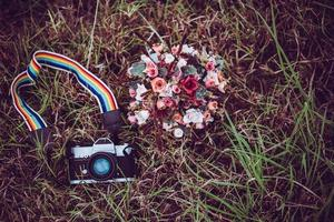 Vintage camera with bouquet of flowers on a grass background photo