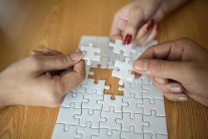 Hands connecting puzzle piece together on wooden table photo