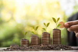 Manos poniendo pilas de monedas de dinero juntas en la naturaleza foto