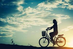 Silhouette of a woman with a bicycle and beautiful sky