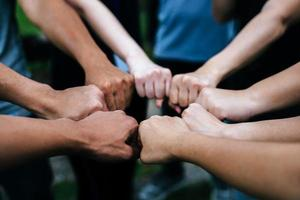 Close-up of multiethnic group standing with hands together