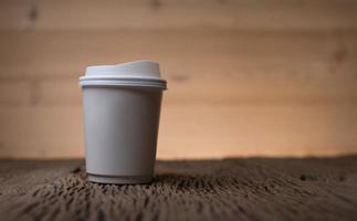 Taza de café de papel en blanco sobre la mesa de madera