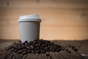 Taza de café de papel con granos de café sobre una mesa de madera
