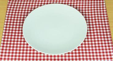 plato blanco sobre tela roja foto