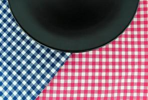 Black plate on checkered tablecloth