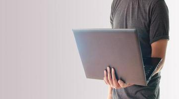 hombre sosteniendo una laptop foto