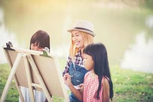 Mother and daughters drawing pictures together in a park