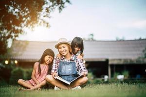 Madre contando una historia a sus dos pequeñas hijas en el jardín de la casa.