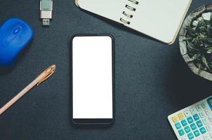 vista superior del teléfono, el cuaderno y el bolígrafo en un escritorio