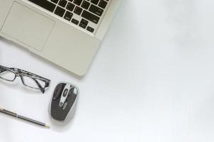 Ordenador portátil y gafas sobre fondo blanco. foto